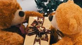 stuffed animal : Funny brown moving teddy bears that hold a box with a gift in their paws. Christmas decorations in mall Stock Footage