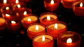 inexpensive : Burning red round candles in catholic church Stock Footage