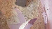 peel off : Male builders hand rips off old pink wallpaper from a wall on repair