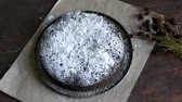 pim : Homemade freshly baked chocolate brownie cake powdered with icing sugar lies next to the stylish dried meadow flowers Stok Video