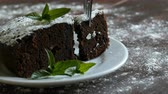 deegrol : Homemade baked chocolate brownie cake muffled with powdered sugar on a white plate decorated with mint leaves. Fork breaks off piece of brownie pie from the plate Stockvideo