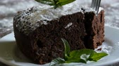 baked : Homemade baked chocolate brownie cake muffled with powdered sugar on a white plate decorated with mint leaves. Fork breaks off piece of brownie pie from the plate Stock Footage