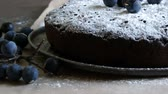 deegrol : Chocolate cake brownie generously covered with powdered sugar stylishly lying next to the blue berries