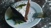 deegrol : A piece of chocolate brownie cake on a white plate decorated with fresh mint leaves next to fork