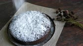 deegrol : Homemade freshly baked chocolate brownie cake powdered with icing sugar lies next to the stylish dried meadow flowers Stockvideo