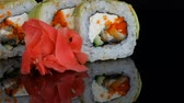 tuňák : Green Dragon Sushi rolls and pink ginger. Sushi roll with salmon, vegetables and avocado closeup. Japan restaurant menu on a mirror surface against a black background. Japanese cuisine in studio Dostupné videozáznamy