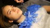 refletindo : Fashion studio, the model is preparing for the show. Teen girl lies on a special couch, designer prepares her image using a special airbrush spray with blue paint