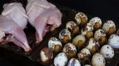 rebhuhn : Fresh meat of quail in a plastic brown tray next to the quail eggs on black background