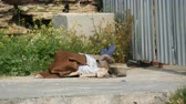 dakloze : Homeless man lies and sleeps on the street under fence covered with material from sun