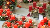 colorful backgrounds : Beautifully decorated Christmas decor compositions of red wax candles and wreaths on store window