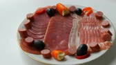 obiad : Meat and sausage slices on plate next to black olives, paprika with cheese and hunting sausages. Salami and sliced ham. Arranged dried meat in restaurant. Appetizing. Cured meat plate Wideo