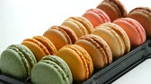 aardbeien : Multicolored french cookies macaron or macaroon in a special black box on white table Stockvideo