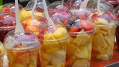 tohumlar : Counter with tropical fruits, mangoes, passion fruit, kiwi, bananas, strawberry in plastic packaging. Healthy fresh diet food ready to eat, assorted cut fruit in plastic glasses for sale.