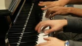 učitel : Playing the piano in four hands. Masterly pianists play at central railway station in Amsterdam