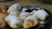 vajas : Female hand takes freshly baked homemade croissants with icing sugar on top on a large plate in the kitchen Stock mozgókép