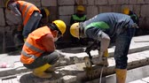 блок : Cuenca, Ecuador  -  20180920  -  Worker Cuts Concrete With Rotary Saw While Second Worker Sprays Water on Blade