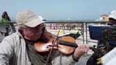 trio : Tel Aviv, Israel - 2019-04-27 - Elderly String Musicians at Beach with Sound 1 - violin closeup. Stock Footage