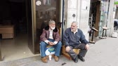성숙한 성인 : Amman, Jordan - 2019-04-18 - Two Elderly Men Sit on Boxes and Talk.