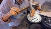 takı : Isfahan, Iran - 2019-04-12 - Elderly Man Uses Hammer and Chisel to Engrage Silver Bowl - Close. Stok Video