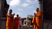 равновесие : Polonnaruwa, Sri Lanka - 2019-03-23 - Monks On Tour 9 - Posing With Buddha Statue Standing. Стоковые видеозаписи