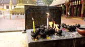 gyertyafény : Chiang Mai, Thailand - 2019-03-15 - Candles Burn In Front of Thai Prayer Plaque.