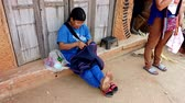werkkleding : Mae Saiong. Thailand - 2019-03-11 - Woman Sits On Ground And Finishes Carpet By Sewing. Stockvideo