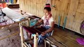 werkkleding : Bangkok, Thailand - 2019-03-03 - Long Neck Karen Tribe Woman 1 - Woman Weaves Tapestry on Her Loom. Stockvideo