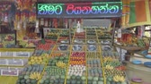výživný : Kataragama, Sri Lanka - 2019-03-29 - Fruit and Vegetable Stand With Asian Advertising Text Scrolling Above.