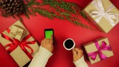 vintage : Top view christmas hands using touchscreen smartphone tablet christmas presents shopping list drinking coffee on red background from above.