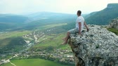 край : young man sits on the edge of a cliff Стоковые видеозаписи