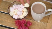 marshmellow : Mans hand put some marshmellows into hot chocolate. Christmas theme.