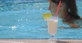 ananás : Fresh white cocktail by the pool. Woman swimming on ththe background. Summer holidays, travel, vacation concept. Stock Footage