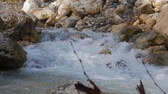apressar : stream on mountain river in spring time and stone thrown to that river