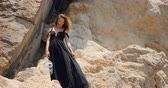 hair cut : Beautiful woman with white cage standing on the rock in windy weather in elegant cut out black dress