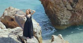 eşarp : Beautiful woman standing on rock in elegant black dress and holding black scarf about her head