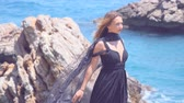 меланхолия : Beautiful girl in elegant black dress with black scarf standing on rock