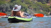 veslo : Young woman in hat sunbathing in canoe or kayaking in Oludeniz sea in Turkey. Dostupné videozáznamy