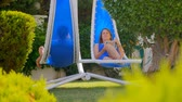 sling : Young woman and man relaxing in rocking chairs, woman reading a book Stock Footage