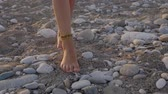 tesouro : Closeup of child feet with beaded bracelets, on the beach at sunset time Stock Footage