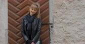 düz saç : Young woman in black leather jacket standing near the stone wall Stok Video