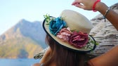 Beautiful woman in hat decorated with flowers near strawy beach umbrella and sea view on background Dostupné videozáznamy
