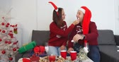 Happy couple in sweaters with dog in Christmas hat sitting on the sofa near beautiful white Christmas tree with red balls at home and drinking hot chocolate. Dostupné videozáznamy