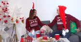 Happy couple in sweaters with dog in Christmas hat sitting on sofa with white Christmas tree with red balls at home and giving presents to each other. Dostupné videozáznamy