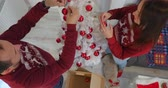 Happy couple in red sweaters decorating white Christmass tree with red balls