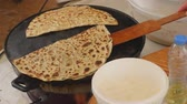 assar : Womans hand with kithcen paddle takes of one prepared gozleme, traditional Turkish food, from a special pan Vídeos