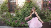 tüll : Fashion lifestyle portrait of young happy pretty woman in pink tulle skirt jumping funnily on street background in slow motion