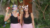 mamada : Two young funny women in pink tulle skirts and funny glasses blowing party bubbles at the camera outdoors on the street