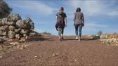 open air museum : Young women in casual clothes walking foreward in the centre of rubble road on blue sky background, slow motion Stock Footage