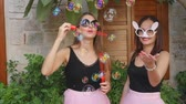 adorável : Two young funny women in pink tulle skirts and funny glasses blowing party bubbles at the camera outdoors on the street