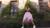 koketa : Fashion lifestyle portrait of young happy pretty woman in pink tulle skirt happily dancing on the street in slow motion